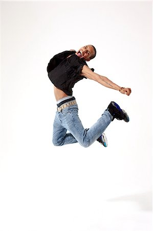 Jubilant young man in mid air Stock Photo - Premium Royalty-Free, Code: 614-05650928