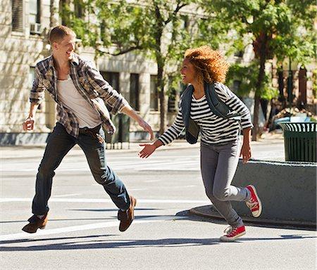 Couple running through city street Stock Photo - Premium Royalty-Free, Code: 614-05650934