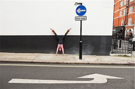 street - Woman performing handstand on pavement Stock Photo - Premium Royalty-Free, Code: 614-05662209