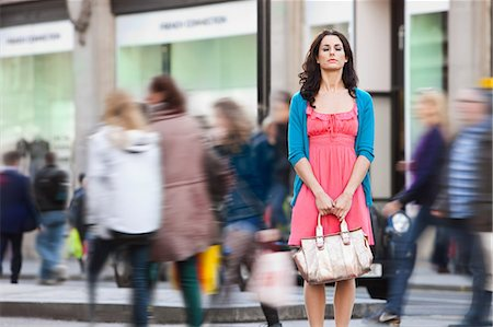 Mid adult woman in pink dress standing still in crowded city Stock Photo - Premium Royalty-Free, Code: 614-05662202