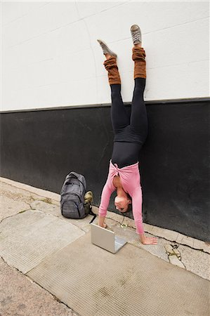 flexible (people or objects with physical bendability) - Woman performing handstand and using laptop on pavement Stock Photo - Premium Royalty-Free, Code: 614-05662210
