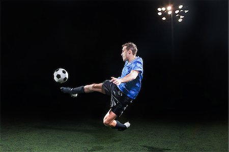 footballeur - Young soccer player leaping into air to kick ball Stock Photo - Premium Royalty-Free, Code: 614-05662287