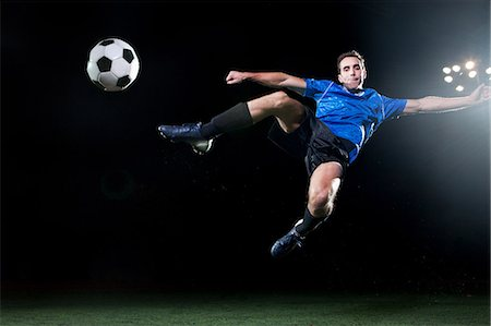 soccer player (male) - Young soccer player leaping into air to kick ball Stock Photo - Premium Royalty-Free, Code: 614-05662289