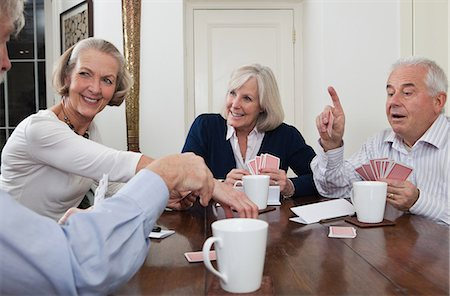Senior friends playing cards Stock Photo - Premium Royalty-Free, Code: 614-05792349