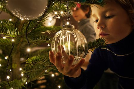 Boy decorating Christmas tree with baubles at home Stock Photo - Premium Royalty-Free, Code: 614-05792381