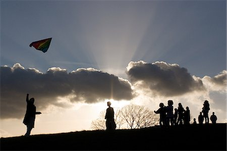 Silhouetted people in park with kite Stock Photo - Premium Royalty-Free, Code: 614-05792396