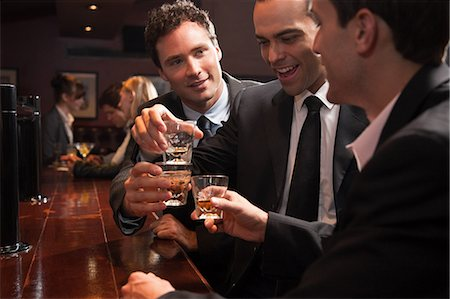 Three businessmen drinking at a bar Stock Photo - Premium Royalty-Free, Code: 614-05792418