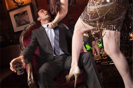 Woman grabbing businessman in bar Stock Photo - Premium Royalty-Free, Code: 614-05792413