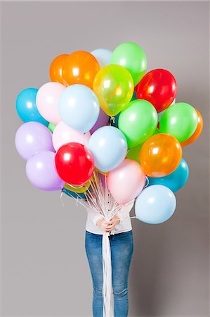 Woman holding large amount of balloons Stock Photo - Premium Royalty-Free, Code: 614-05792513