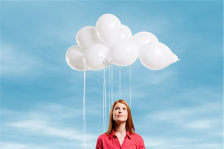Young woman looking at thought bubble made of balloons Stock Photo - Premium Royalty-Free, Code: 614-05792521