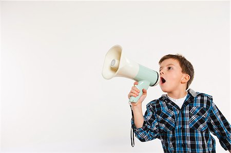 Boy shouting through megaphone Stock Photo - Premium Royalty-Free, Code: 614-05818924