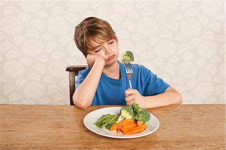 sad child sitting - Boy frowning at vegetables Stock Photo - Premium Royalty-Free, Code: 614-05818925