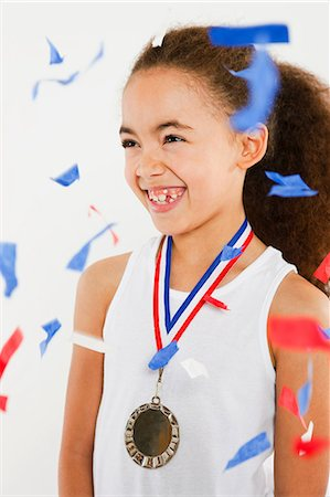 Girl wearing medal with ticker tape falling Stock Photo - Premium Royalty-Free, Code: 614-05818956