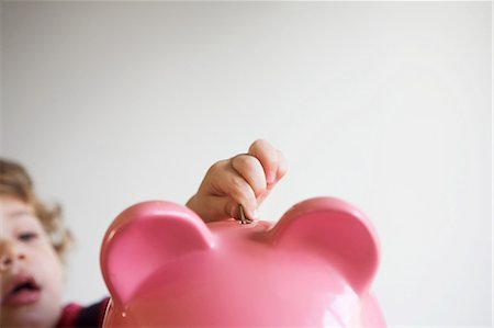 Little boy putting money in piggy bank Stock Photo - Premium Royalty-Free, Code: 614-05819032