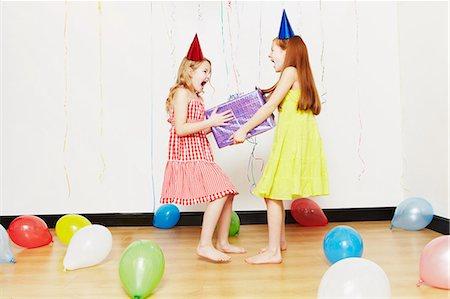 Girls fighting over birthday gift Stock Photo - Premium Royalty-Free, Code: 614-05819069