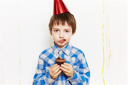 Boy with cupcake around his mouth Stock Photo - Premium Royalty-Free, Code: 614-05819073