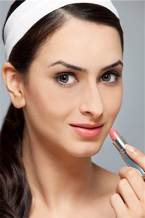 Beautiful woman applying lipstick Stock Photo - Premium Royalty-Free, Code: 614-05955239