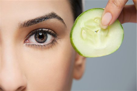Woman with a cucumber next to her eye Stock Photo - Premium Royalty-Free, Code: 614-05955231