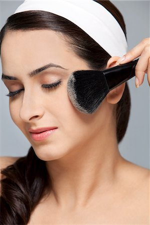 Beautiful woman applying blush Stock Photo - Premium Royalty-Free, Code: 614-05955240