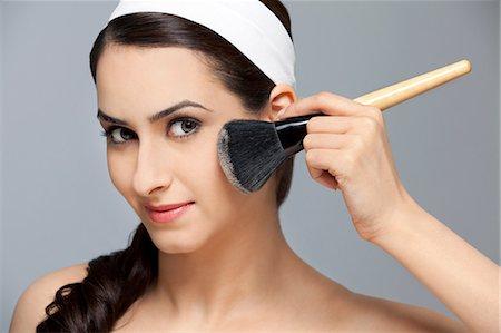 Beautiful woman applying blush Stock Photo - Premium Royalty-Free, Code: 614-05955241