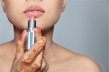 Close-up of a woman applying lipstick Stock Photo - Premium Royalty-Free, Code: 614-05955257