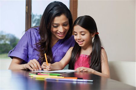 Girl writing while her mother looks on Stock Photo - Premium Royalty-Free, Code: 614-05955294