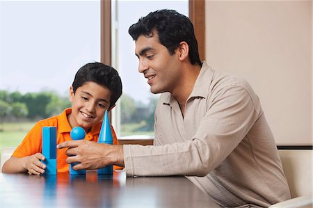 Father and son playing with building blocks Stock Photo - Premium Royalty-Free, Code: 614-05955297