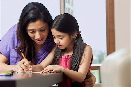 Mother teaching her daughter to write Stock Photo - Premium Royalty-Free, Code: 614-05955293