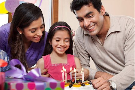 Girl celebrating her birthday with parents Stock Photo - Premium Royalty-Free, Code: 614-05955300