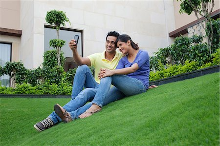 style - Couple taking a self portrait on a lawn Stock Photo - Premium Royalty-Free, Code: 614-05955338