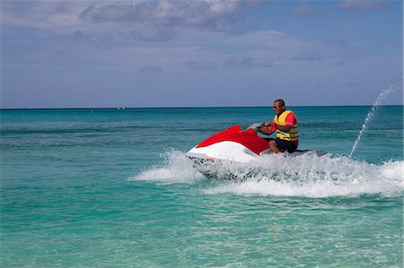 extremism - Man jet skiing in Caribbean sea, Grand Cayman, Cayman Islands Stock Photo - Premium Royalty-Free, Code: 614-05955467