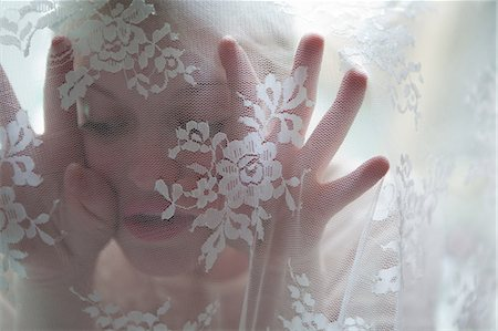 quirky - Young woman behind lace curtain Stock Photo - Premium Royalty-Free, Code: 614-05955488