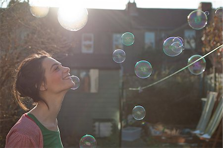 Young woman outdoors with bubbles floating in air Stock Photo - Premium Royalty-Free, Code: 614-05955499