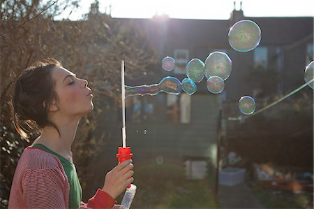 Young woman blowing bubbles outdoors Stock Photo - Premium Royalty-Free, Code: 614-05955500