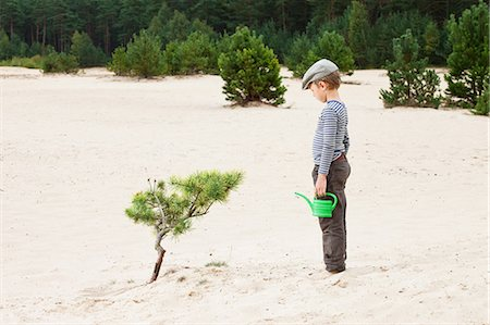 Boy with watering can, looking at plant in sand Stock Photo - Premium Royalty-Free, Code: 614-05955512