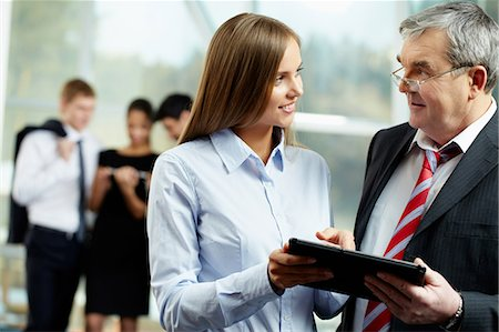 staff - Young woman talking to a senior businessman Stock Photo - Premium Royalty-Free, Code: 614-05955522