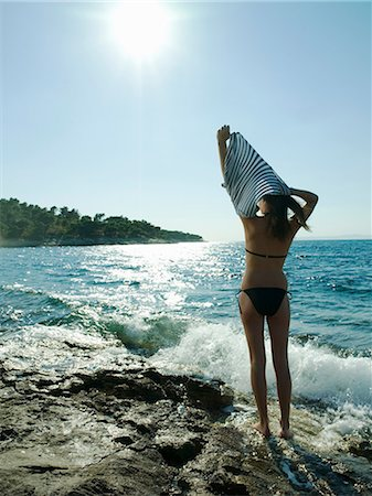 Young woman taking off t-shirt by the sea Stock Photo - Premium Royalty-Free, Code: 614-05955569