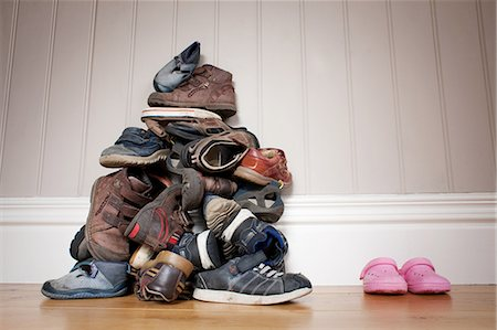 family shoes - Large pile of boy's shoes beside one pair of girl's shoes Stock Photo - Premium Royalty-Free, Code: 614-05955603