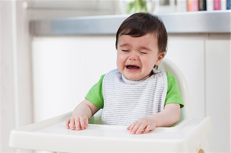 sad child sitting - Baby boy in high chair, crying Stock Photo - Premium Royalty-Free, Code: 614-05955619