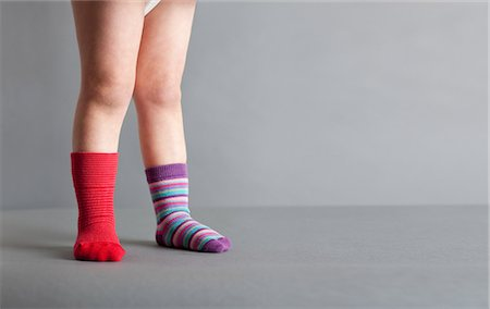 Child wearing one red sock and one striped sock Stock Photo - Premium Royalty-Free, Code: 614-05955610