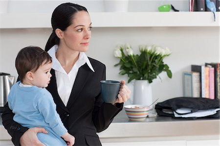 dark hair - Businesswoman holding baby son and coffee cup Stock Photo - Premium Royalty-Free, Code: 614-05955624