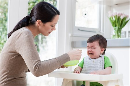 Mother feeding crying baby son Stock Photo - Premium Royalty-Free, Code: 614-05955650