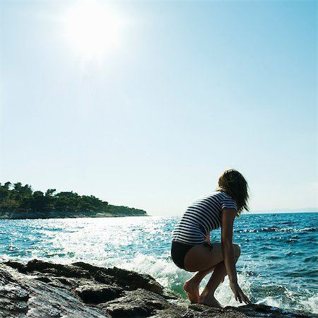 Young woman crouching by the sea Stock Photo - Premium Royalty-Free, Code: 614-05955735