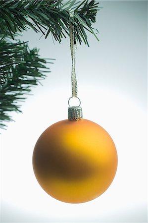 Yellow christmas bauble hanging on tree Stock Photo - Premium Royalty-Free, Code: 614-05955767
