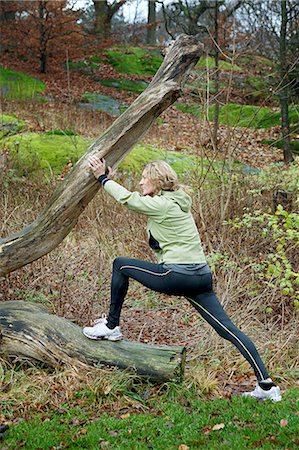 Mature woman stretching against tree in forest Stock Photo - Premium Royalty-Free, Code: 614-06002109