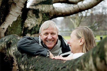 Senior couple leaning against tree, smiling Stock Photo - Premium Royalty-Free, Code: 614-06002128