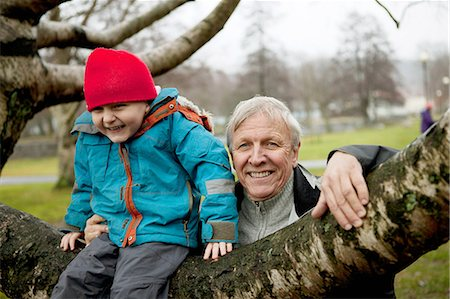 Granfather and boy sitting on tree branch, smiling Stock Photo - Premium Royalty-Free, Code: 614-06002131