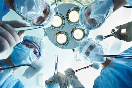 Low angle view of four surgeons bending over the patient during operation Stock Photo - Premium Royalty-Free, Code: 614-06002156