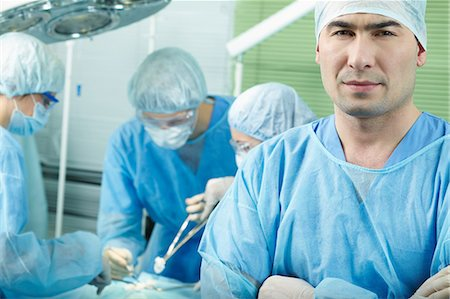 Surgeon looking at camera, colleagues in background performing operation Stock Photo - Premium Royalty-Free, Code: 614-06002158