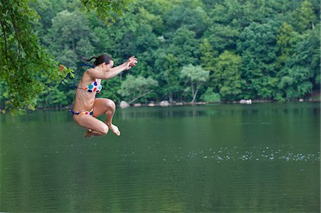 Mid adult woman leaping into river Stock Photo - Premium Royalty-Free, Code: 614-06002187